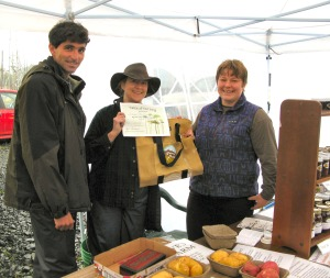 Fabian Grutter, left, and Evening Star Grutter, right, of Eve's Farm receive the Table of the Day Award from Linda Wilson during the fourth Sitka Farmers Market of the season on Aug. 29.
