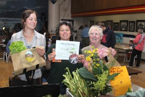 Hope Merritt, left, and Judy Johnstone, right, of Gimbal Botanicals and Sprucecot Gardens receive the Table of the Day Award from Ellen Frankenstein during the third Sitka Farmers Market of the season on Aug. 15.