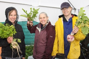 Natalie Sattler, left, holds parsnips, while Lisa Sadleir-Hart, center, and Doug Osborne, right, hold turnips for sale at the Sitka Local Foods Network booth