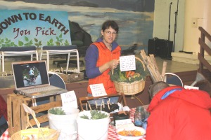 Lori Adams of Down To Earth U-Pick Gardens shows off a basket of produce she was giving away