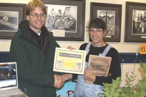 Sitka Local Foods Network Board Member Doug Osborne presents Lori Adams of Down To Earth U-Pick Garden the Table Of The Day award for the first Sitka Farmers Market of the 2010 summer season