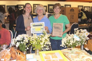 Sitka Local Foods Network boardmember Johanna Willingham, left, presents Karen Christner, center, and Malinda Bonsen, right, of Malinda and Karen's Bakery with the Table of the Day award at the second Sitka Farmers Market of the summer on July 31 at Alaska Native Brotherhood Hall in Sitka.