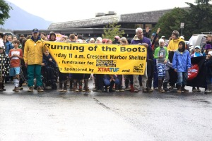 Participants line up behind the Running of the Boots banner before the start of the race