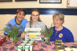 Sitka Local Foods Network board members Maybelle Filler, left, and Suzan Brawnlyn, right, present home baker and honey/jelly maker Iris Klingler with the Table of the Day Award for the fifth Sitka Farmers Market of the summer on Sept. 11, 2010.