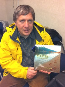 "Author/photographer Larry Johansen poses with a copy of his new book, ""XTRATUF: An Alaskan Way of Life,"" during the Sitka Artisans Market on Dec. 4"