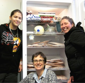 Pacific High School student Jessie Young, left, co-principal Sarah Ferrency, center, and lunch coordinator Johanna Willingham load rockfish into the freezer at Pacific High School. an alternative high school in Sitka, Alaska. (PHOTO COURTESY OF TRACY GAGNON / SITKA CONSERVATION SOCIETY)