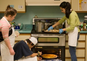 LOCALLY MADE– Americorps Volunteer Lauren Hahn, left, and Pacific High School students in the culinary arts program, Brendan Didrickson and Jenny Jeter, prepare a lunch of Caribbean rockfish with sweet potato fries, baked apples and wild rice at the school on Wednesday, Feb. 1. This was the first Pacific High lunch in the Fish to Schools program. The program began in 2010 as a Sitka Health Summit project when Sitka Conservation Society joined Blatchley Middle School to serve locally caught fish in school lunches. Since then, Keet Gooshi Heen Elementary School and now Pacific High have joined the twice-monthly program. On Wednesday, Feb. 8, SCS is inviting commercial fishers to join students at Keet for lunch. (Daily Sitka Sentinel photo by James Poulson, printed in the Tuesday, Feb. 7, 2012, edition)