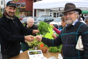 Kerry MacLane uses a token to purchase produce from Sitka Farmers Market vendor Keith Nyitray during the Aug. 3, 2013, Sitka Farmers Market.