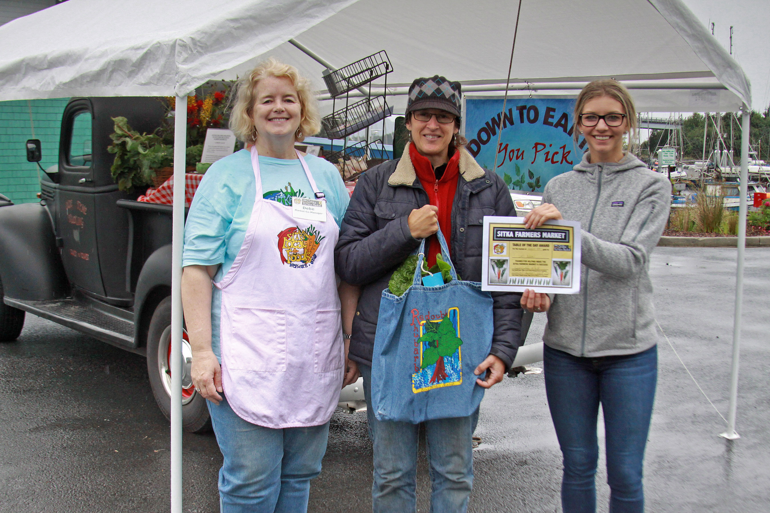 Sitka Farmers Market Co-Managers Debe Brincefield, left, and Ellexis Howey, right, present the Table Of The Day Award to Lori Adams of Down-To-Earth U-Pick Garden at the fourth Sitka Farmers Market of the 2014 summer on Saturday, Aug. 9, at the Alaska Native Brotherhood Founders Hall in Sitka. Lori has been selling fresh produce, jams and jellies, and her local book on gardening at the Sitka Farmers Market for several years. She received a gift bag with fresh greens, fresh rhubarb, a pair of earrings, a dozen eggs, and a copy of the Alaska Farmers Market Cookbook. This is the seventh year of Sitka Farmers Markets, hosted by the Sitka Local Foods Network. The next market is from 10 a.m. to 1 p.m. on Saturday, Aug. 23, at the Alaska Native Brotherhood Founders Hall, 235 Katlian St. Check our website to learn about our new bus service to the market. For more information about the Sitka Farmers Markets and Sitka Local Foods Network, go to http://www.sitkalocalfoodsnetwork.org/, or check out our Facebook page at https://www.facebook.com/SitkaLocalFoodsNetwork. (PHOTO COURTESY OF SITKA LOCAL FOODS NETWORK)