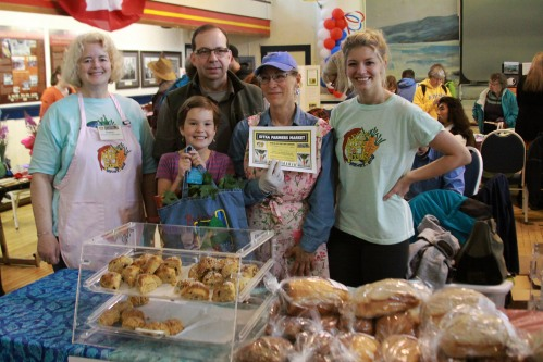 Sitka Farmers Market Co-Managers Debe Brincefield, left, and Ellexis Howey, right, present the Table Of The Day Award to Pat Hanson, second from right, of Hanson Baked Goods while Jim Hanson, second from left, and friend Taylor Ihde look on at the second Sitka Farmers Market of the 2014 summer on Saturday, July 26, at the Alaska Native Brotherhood Founders Hall in Sitka. Pat has been selling homemade bread, cinnamon rolls and scones at the Sitka Farmers Market for a couple of years. She received a gift bag with fresh greens, fresh rhubarb, and a copy of the Alaska Farmers Market Cookbook. This is the seventh year of Sitka Farmers Markets, hosted by the Sitka Local Foods Network. The next market is from 10 a.m. to 1 p.m. on Saturday, Aug. 9, at the Alaska Native Brotherhood Founders Hall, 235 Katlian St. This week, Aug. 3-9, is National Farmers Market Week, so celebrate by coming to the Sitka Farmers Market. Check our website to learn about our new bus service to the market. For more information about the Sitka Farmers Markets and Sitka Local Foods Network, go to http://www.sitkalocalfoodsnetwork.org/, or check out our Facebook page at https://www.facebook.com/SitkaLocalFoodsNetwork. (PHOTO COURTESY OF SITKA LOCAL FOODS NETWORK)