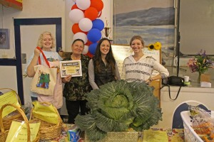Sitka Farmers Market Co-Managers Debe Brincefield, left, and Ellexis Howey, right, present the Table Of The Day Award to Florence Welsh and her daughter Cory Welsh of Welsh Family Forget-Me-Not Gardens at the sixth and final Sitka Farmers Market of the 2014 summer on Saturday, Sept. 5, at the Alaska Native Brotherhood Founders Hall in Sitka. The Welsh family has one of the larger gardens in Sitka, raising a variety of veggies including cabbage, carrots, zuccini, potatoes, greens, and more. Florence received a gift bag with fresh greens, fresh carrots, fresh rhubarb, and a copy of the Alaska Farmers Market Cookbook. This concludes the seventh year of Sitka Farmers Markets, hosted by the Sitka Local Foods Network. While the Sitka Farmers Market is over for the summer, we will host a produce table at the 20th annual Running of the Boots, with registration at 10 a.m., costume judging at 10:30 a.m. and race at 11 a.m. on Saturday, Sept. 27, near St. Michael of the Archangel Russian Orthodox Cathedral on Lincoln Street. For more information about the Sitka Farmers Markets and Sitka Local Foods Network, go to http://www.sitkalocalfoodsnetwork.org/, or check out our Facebook page at https://www.facebook.com/SitkaLocalFoodsNetwork. (PHOTO COURTESY OF SITKA LOCAL FOODS NETWORK)