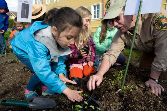 Sitka National Historical Park volunteer gardener Pam Vanderweele helps Baranof Elementary School kindergartner Arianna Moctezuma-Hernandez, 6, plant peas in the Russian Bishop's House garden on a recent sunny morning. The kindergartners will return to the historical garden in the fall when they are in the first grade to harvest the crops and cook them in a soup. (Daily Sitka Sentinel Photo by James Poulson)
