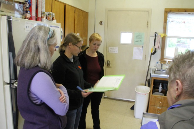 Sitka Kitch Advisory Team Members, from left, Lisa Sadleir-Hart, Kristy Miller, Sarah Lewis, and Dorrie Farrell go through the orientation packet before a recent series of canning and cottage foods classes taught by Lewis.