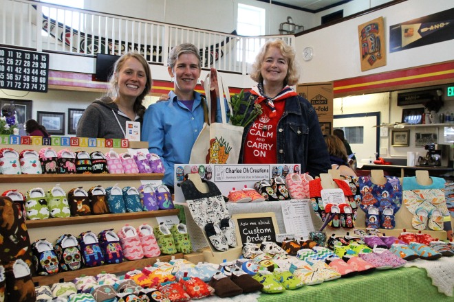 "Sitka Local Foods Network Board Secretary Alli Gabbert, left, and Sitka Farmers Market Manager Debe Brincefield, right, present the Table Of The Day Award to Jennifer ""Springer"" Black of Charlee Oh Creations at the first Sitka Farmers Market of the 2015 summer on Saturday, July 4, at the Alaska Native Brotherhood Founders Hall in Sitka. Springer is a new vendor at the Sitka Farmers Market and she sold handmade soft-soled shoes for babies and toddlers, some with matching bibs. Springer received a gift bag with fresh greens, fresh rhubarb, fresh mint, and some handmade earrings donated by Taylor Ihde. This is the eighth year of Sitka Farmers Markets, hosted by the Sitka Local Foods Network. The next market is from 10 a.m. to 1 p.m. on Saturday, July 18, at the Alaska Native Brotherhood Founders Hall, 235 Katlian St. Bring your canner pressure gauge to this market to have it checked. For more information about the Sitka Farmers Markets and Sitka Local Foods Network, go to http://www.sitkalocalfoodsnetwork.org/ or check out our Facebook page at https://www.facebook.com/SitkaLocalFoodsNetwork. (PHOTO COURTESY OF SITKA LOCAL FOODS NETWORK)"