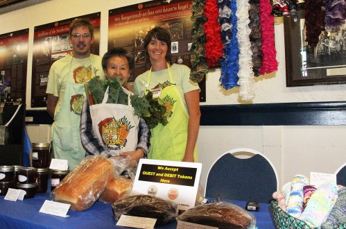 Sitka Farmers Market Assistant Manager Francis Wegman-Lawless, left, and Sitka Local Foods Network Board Member Brandie Cheatham, right, present the Table Of The Day Award to Phyllis Moore at the fourth Sitka Farmers Market of the 2015 summer on Saturday, Aug. 15, at the Alaska Native Brotherhood Founders Hall in Sitka. Moore sells jams and jellies, baked goods, and a variety of knitted items from hats and potholders to Afghan blankets. She received a gift bag with fresh greens and fresh rhubarb. This is the eighth year of Sitka Farmers Markets, hosted by the Sitka Local Foods Network. The next market is from 10 a.m. to 1 p.m. on Saturday, Aug. 29, at the Alaska Native Brotherhood Founders Hall, 235 Katlian St. Don't forget the Sitka Slug Races take place at 12:30 p.m. at the Aug. 29 Sitka Farmers Market. For more information about the Sitka Farmers Markets and Sitka Local Foods Network, go to http://www.sitkalocalfoodsnetwork.org/, check out our Facebook page at https://www.facebook.com/SitkaLocalFoodsNetwork, or follow us on Twitter at https://www.twitter.com/SitkaLocalFoods. (PHOTO COURTESY OF SITKA LOCAL FOODS NETWORK)