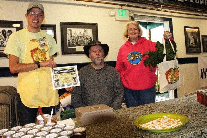 Sitka Farmers Market Assistant Manager Francis Wegman-Lawless, left, and Sitka Farmers Market Manager Debe Brincefield, right, present the Table Of The Day Award to Rock Peterson of Jam-N-Peppers at the fifth Sitka Farmers Market of the 2015 summer on Saturday, Aug. 29, at the Alaska Native Brotherhood Founders Hall in Sitka. Peterson sells an apricot and pepper jam/glaze. He received a gift bag with fresh chard, kale, beets, and other veggies. The market also featured the inaugural Sitka Slug Races, won by Linda Wilson's slug Moses, with Sophie Nethercut and Maybelle Filler's slug Thug The Slug second, and Thomas Witherspoon's slug Slugzilla third. This is the eighth year of Sitka Farmers Markets, hosted by the Sitka Local Foods Network. The last market of the summer is from 10 a.m. to 1 p.m. on Saturday, Sept. 12, at the Alaska Native Brotherhood Founders Hall, 235 Katlian St. For more information about the Sitka Farmers Markets and Sitka Local Foods Network, go to http://www.sitkalocalfoodsnetwork.org/, check out our Facebook page at https://www.facebook.com/SitkaLocalFoodsNetwork, or follow us on Twitter at https://www.twitter.com/SitkaLocalFoods. (PHOTO COURTESY OF SITKA LOCAL FOODS NETWORK)