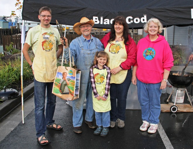 Sitka Farmers Market Assistant Manager Francis Wegman-Lawless, left, and Sitka Farmers Market Manager Debe Brincefield, right, present the Table Of The Day Award to Kerry MacLane, second from left, and his Sitka's Blackcod Collars helpers Autumn Mayo, center, and Ilona Mayo, second from right, at the sixth and final Sitka Farmers Market of the 2015 summer on Saturday, Sept. 12, at the Alaska Native Brotherhood Founders Hall in Sitka. MacLane is a regular participant at the Sitka Farmers Market with his grilled blackcod collars/tips served over rice with beach asparagus, kale, and other greens for a garnish. This was the eighth year of Sitka Farmers Markets, hosted by the Sitka Local Foods Network. While the Sitka Farmers Markets are over for 2015, the Sitka Local Foods Network will host a produce booth at the Running of the Boots on Saturday, Sept. 26, near St. Michael's Russian Orthodox Church. The Running of the Boots is a costumed fun run fundraiser for the Sitka Local Foods Network, where people run a short race in their XtraTufs (aka Sitka Sneakers). Registration opens at 10 a.m., with costume judging about 10:30 a.m. and the race start at 11 a.m. For more information about the Sitka Farmers Markets, Running of the Boots, and Sitka Local Foods Network, go to http://www.sitkalocalfoodsnetwork.org/, check out our Facebook page at https://www.facebook.com/SitkaLocalFoodsNetwork, or follow us on Twitter at https://www.twitter.com/SitkaLocalFoods. (PHOTO COURTESY OF SITKA LOCAL FOODS NETWORK)