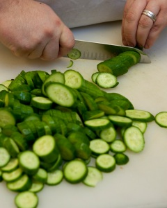 Cutting slices of fresh cucumber. Cucumbes, food prep, knife, cooking, vegetables. UF/IFAS Photo by Tyler Jones.